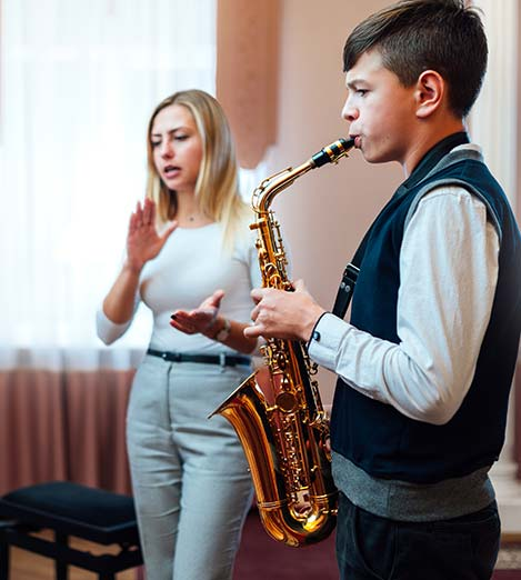 Boy playing jazz with music education instructor
